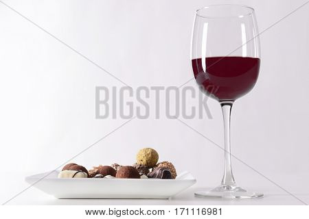 Delicious chocolate candies and red wine on white background