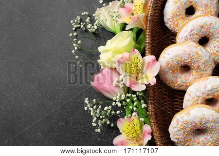 Wicker basket with delicious doughnuts and beautiful flowers on grey background