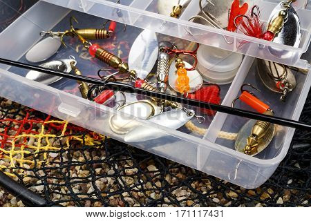 Open storage box with accessories for fishing and fishing baits on the stony ground