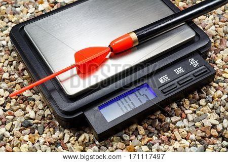 Weighting a fishing float on a pocket scale on the stony ground