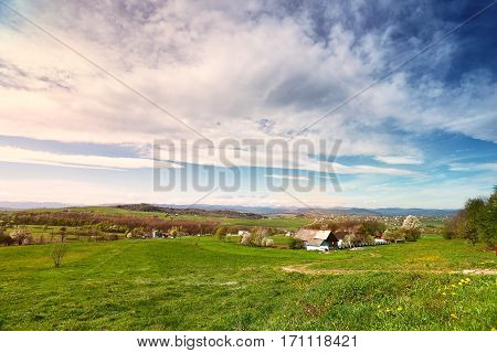 Sunny spring day in village and town on foothills. Mountains on background. Sunny green spring landscape.