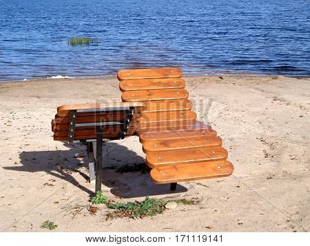 Wooden sunbeds on the shore of the lake