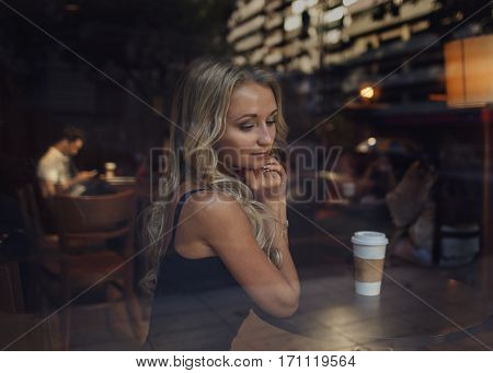 Beautiful blonde girl sitting at the cafe with a cup of coffee and a figure of man behind her on the background. Romantic concept. Blind date. Lonely in Saint Valentine. Relationship concept.