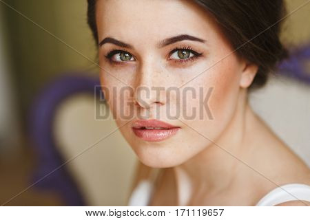 Woman with nice make-up looking at camera. Portrait. Indoor, interior, studio, unfocused background