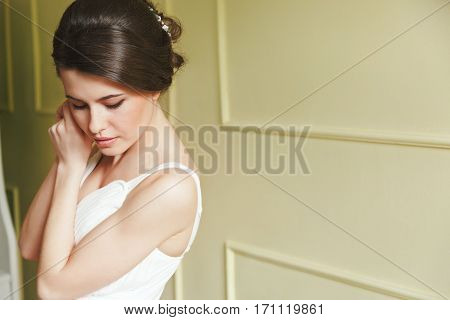 Woman in white dress standing near wall. Looking down. Hands near face. Indoor, interior, studio