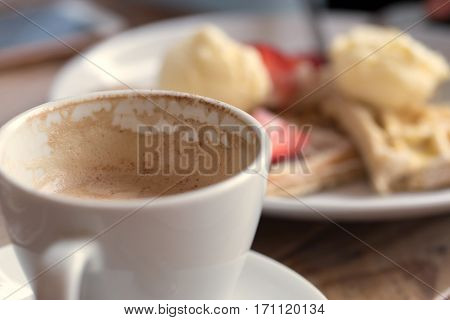 Cup of cappuccino and ice cream on wooden table