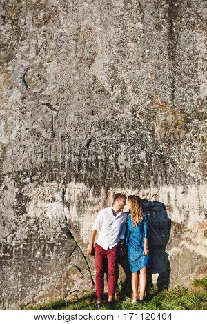 Nice couple standing near stone wall, outdoor. Beloved touching each other with nose and smiling. They holding hands of each other. Woman wearing blue dress and light blue shoes and man wearing white shirt, black shoes and claret trousers. Full body. Copy