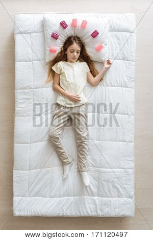 Colorful dreams. Amazing serene blonde girl sleeping on a white bed while wearing cozy pajamas and being surrounded with hair curlers