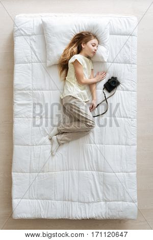 As soon as I wake up. Beautiful calm blonde girl sleeping soundly in her soft bed while imagining herself being a photographer and holding a camera in her hands