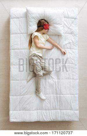 Sweet morning. Beautiful gracious nice child sleeping soundly while wearing cute cozy pajamas and red silk sleeping mask