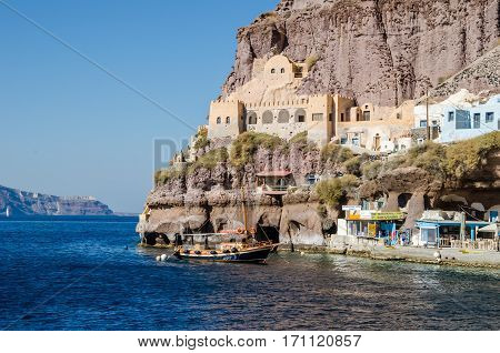 Thira Greece - November 10 2015: View of a part of the harbour with the old boat and traditional buildings build on a conical mountain revealing its volcanic structure