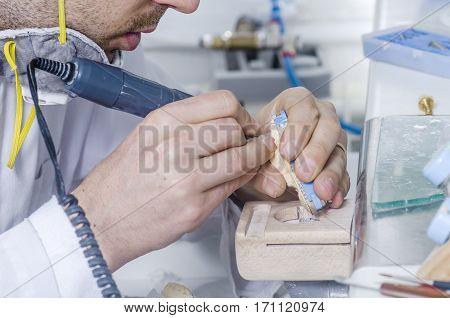 Dental Technician Working In A Metal Ceramic Crowns