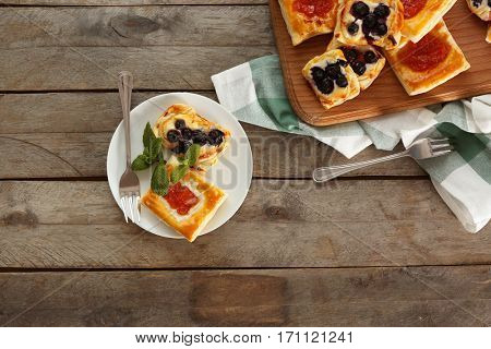 Sweet tasty pastries on wooden background, top view