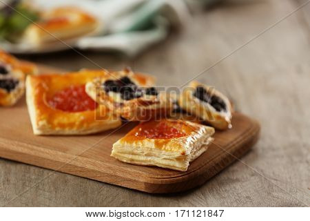 Sweet tasty pastries on cutting board, closeup