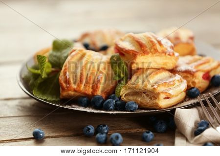 Sweet tasty pastries with bilberries on plate, closeup