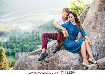 Nice couple sitting on high rock, outdoor. Girl leaning on her boyfriend's knee. Man holding her hand. Beloved looking down. Woman wearing blue dress and light blue shoes and man wearing white shirt, black shoes and claret trousers. Full body