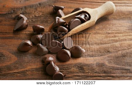Tasty chocolate chips and scoop on wooden background