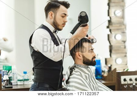 Attractive dark haired man wearing white shirt doing a haircut with hair dryer for man with black hair at barber shop, mirror at background.