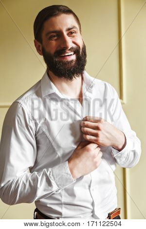 Man buttoning his shirt. Bridegroom smiling. Man in white shirt with beard and moustache. Indoor, studio