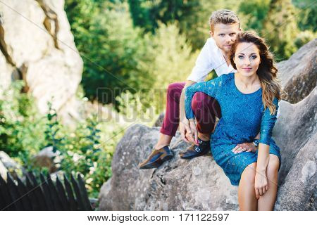 Nice couple sitting on high rock, outdoor. Girl leaning on her boyfriend's knee. Man holding his hand on girls knee and holding her hand with his other hand. Beloved looking at camera. Woman wearing blue dress and man wearing white shirt, black shoes and