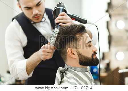 Handsome man wearing white shirt doing a haircut with hair dryer and hair brush for man with black hair at barber shop, mirror at background, portrait.