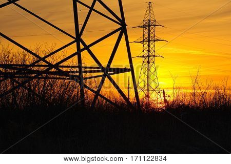 Industrial landscape sunset on the background of high-voltage towers