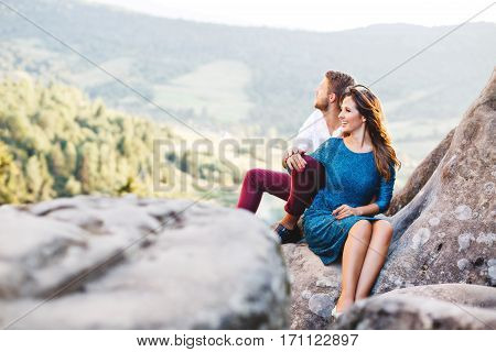 Nice couple sitting on high rock, outdoor. Girl leaning on her boyfriend's knee. Man putting his hand on girl's hand. Beloved looking afield and smiling. Woman wearing blue dress and man wearing white shirt, black shoes and claret trousers. Profile