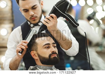 Attractive man wearing white shirt doing a haircut with hair dryer and hair brush for man with black hair at barber shop, mirror and lights at background.