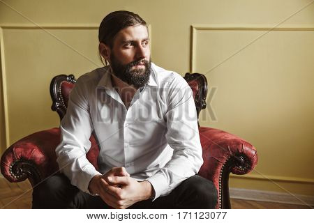 Man sitting on red chair. Bridegroom looking aside. Fingers crossed. Man in white shirt with beard and moustache. Indoor, studio