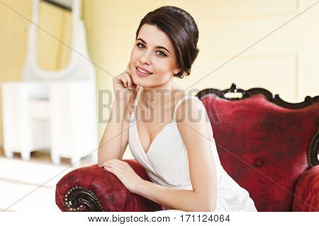 Woman in white dress sitting on red armchair. Looking at camera and smiling. Turned aside. Kneeling on armchair, hand near face. Indoor, interior, studio