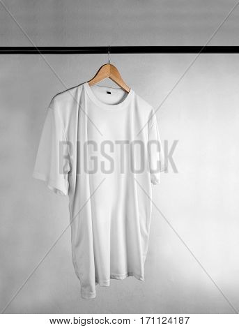 Plain white t-shirt on a wooden clothes hanger. Grey grunge background.