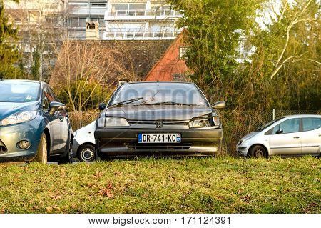 STRASBOURG FRANCE - FEB 12 2017: Vintage old Peugeot car with damaged front and headlight parked in urban enviroment. Peugeot is one of the bigest car manufacturer in the world