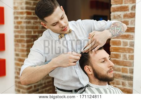 Handsome dark haired man with tattoo wearing white shirt doing a haircut for man with black hair at barber shop, copy space.