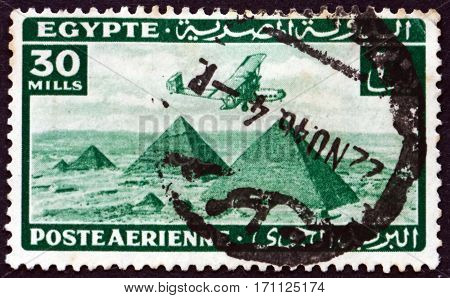 EGYPT - CIRCA 1941: a stamp printed in Egypt shows Airplane over Giza pyramids circa 1941