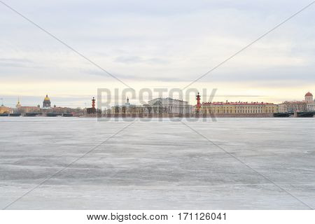 View of Frozen Neva River and Spit of Vasilyevsky Island in center of St.Petersburg at cloudy winter day Russia.