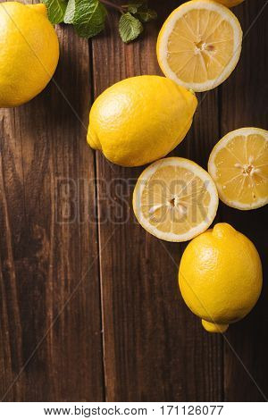 Lemons on a wooden background. Lemons. Fruits. Lemon halves. Mint. Healthy food concept. Copyspace