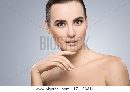 Model looking at camera. Head a little bit aside. Wearing pigtail, nice make-up. Light smile. Fingers touching chin. Beauty portrait, head and shoulders. Indoor, studio