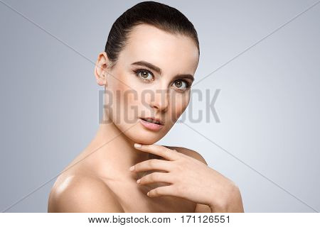 Model looking at camera. Head a little bit aside. Wearing pigtail, nice make-up. Thoughtful girl. Finger touching chin. Beauty portrait, head and shoulders. Indoor, studio