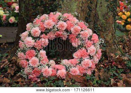 Pink sympathy or funeral flowers near a tree at a cemetery