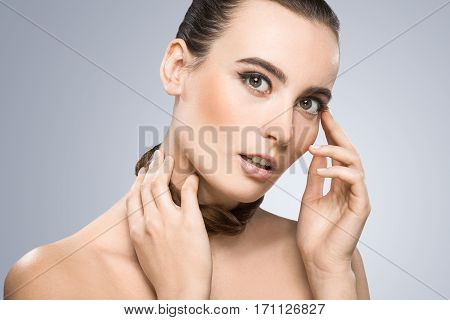 Model looking at camera and holding pigtail around her neck. Touching her face and neck. Nice make-up, looking lively. Beauty portrait, head and shoulders. Indoor, studio