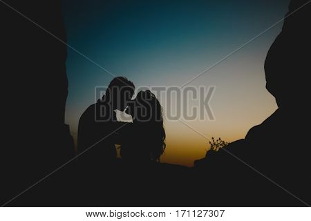 Sunset, shadows of couple. Man and woman embracing and almost kissing in twilight near rocks. Evening, dark sky. Almost night
