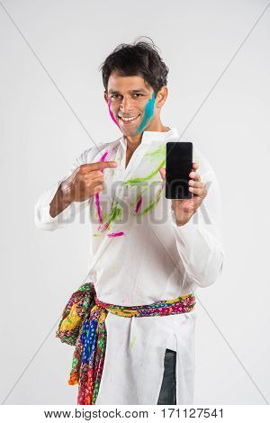 indian handsome man showing mobile screen on holi festival with face painted and in traditional wear, standing isolated over white background