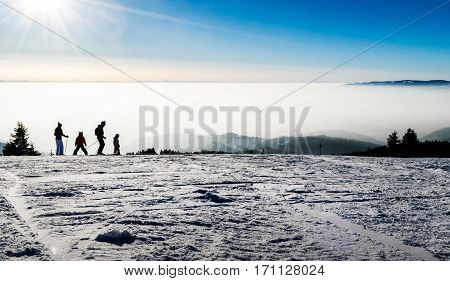 Family skiing silhouettes at a the piste with fog and clouds in the background, Sunny Valley piste, Kopaonik, Serbia