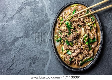 Traditional chinese mongolian beef stir fry on iron plate with rice and soya sauce on slate background. Top view copy space