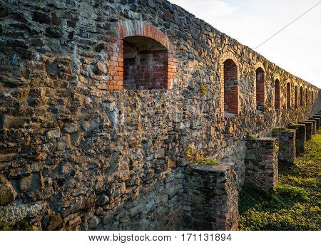 Stone castle wall with embrasure at sunset.