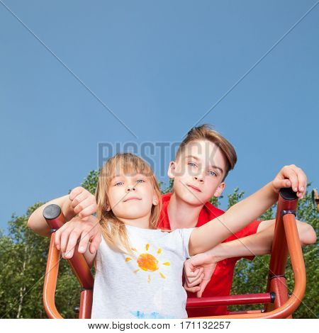 Low angle view of brother and sister posing on a climbing frame in a summer playground looking at camera