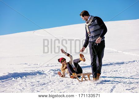 Man pulling girl on a sled at snow - concept: Winter fun.