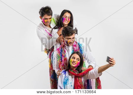Indian man spraying colours with pichkari on girls on holi festival, girls holding sweets and gulal colours in plate and trying to escape, having fun, isolated over white background
