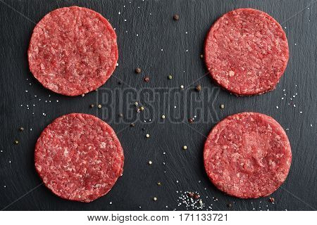 Four fresh raw Prime Black Angus beef burger patties on black stone background. Top view.