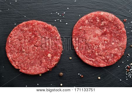 Two fresh raw Prime Black Angus beef burger patties on black stone background. Top view.
